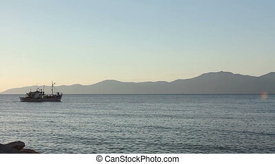 Fishing boat is in transport passing over sea at sunset