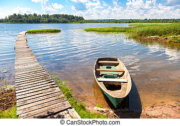 Fishing boat moored at a pier on the lake in the morning in summer sunny day