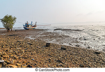 Fishing boat moored at low tide
