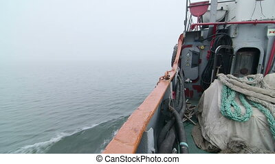 Commercial fishing boat moving forward in the misty sea of Azov