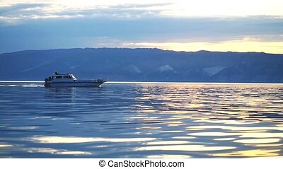 Fishing boat on blue, calm lake during sunset. Island in the...