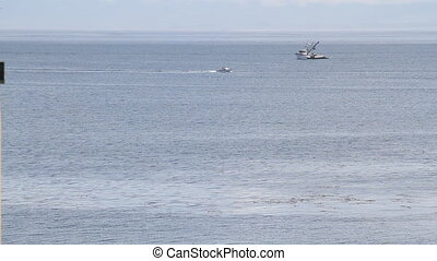 fishing boat on ocean with speedboat