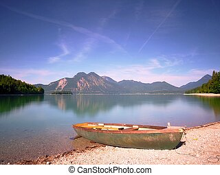 Fishing boat on shore on background of picturesque landscape