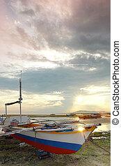 Fishing boat on sunset beach