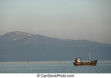 fishing boat on the background of big mountain