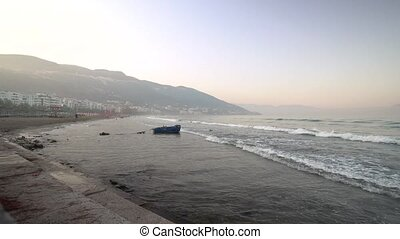 Fishing boat on the beach and sea waves in the morning.