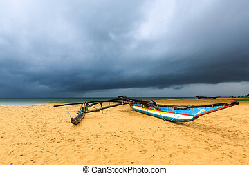 Fishing boat on the beach with dark clouds above the ocean