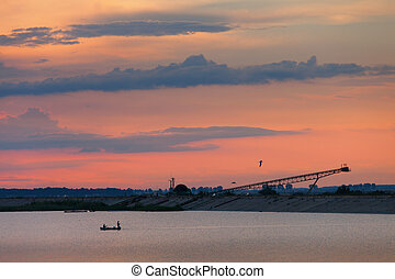 Fishing boat on the lake in sunset with red clouds and birds fly