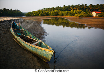 fishing boat on the river bank in the tropics with palm trees in the evening,