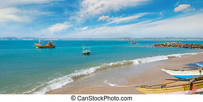 Fishing boat on the sandy shore against a background the ocean and sky. Wide photo.
