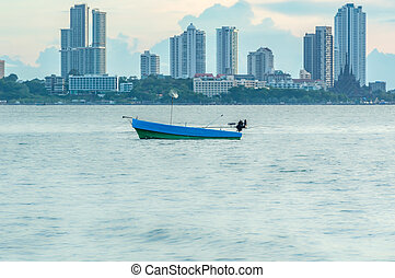 Fishing boat on the sea view of city.