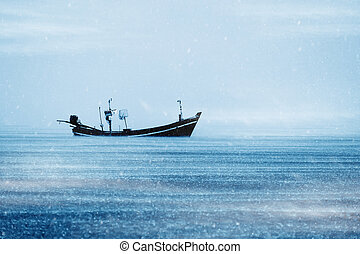 Fishing boat on the sea with snowfall in winter color tone.