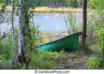 Fishing boat on the shore of a forest lake
