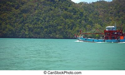Fishing Boat Passing a Forested Tropical Island in Timelapse