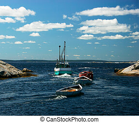 Fishing boats moving out of the harbor in Peggy's Cove, Nova Scotia, Canada.