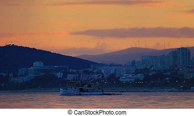 Fishing boat sailing at sunset