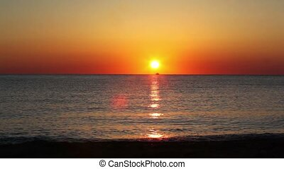 Fishing boat sails on horizon, sunset reflected in sea water...