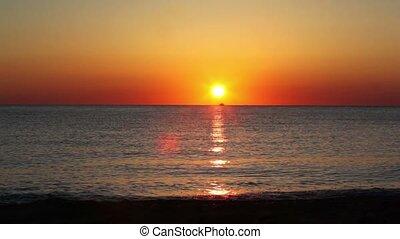 Fishing boat sails on horizon, sunset