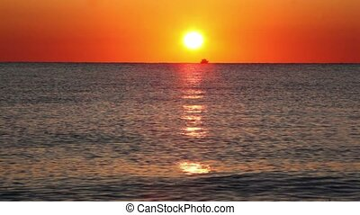 Fishing boat sails on horizon, sunset reflected in sea...