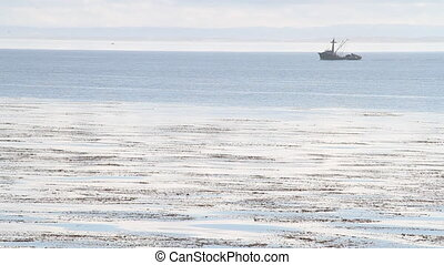 fishing boat travels on calm ocean