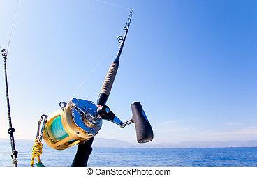fishing boat trolling in ocean with golden reel rod