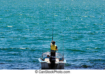 Fishing boat with fisherman holding rod in action.
