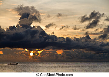 Fishing boat with threatening clouds over South China Sea at...