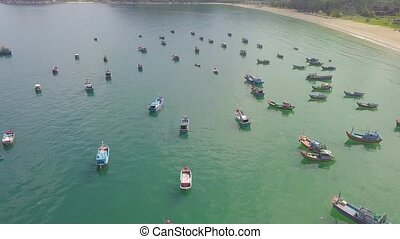 Fishing boats and sail ships in blue sea water at parking aerial landscape. Drone view sea boats and sailing ships in parking.