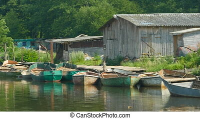 fishing boats at pier with an old barn