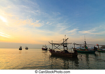 Fishing boats at sunset or sunrise, in Thailand.