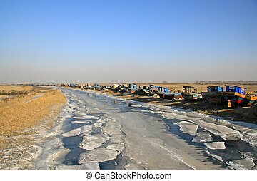 fishing boats berth by the river in winter, north china