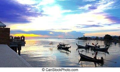fishing boats bobbing in the sea at sunset, fishermen preparing to sail.