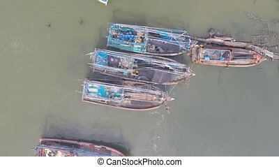 Fishing boats in green water, aerial video. View from above