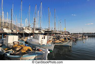 Image shows fishing boats moored in the marina of the city of Kalamata, Greece
