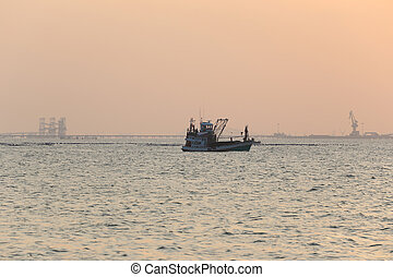 Fishing boats in the sea during the evening.