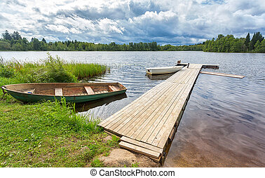 Fishing boats moored at a wooden pier on the lake in summer day