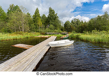 Fishing boats moored at a wooden pier on the lake in summer sunny day