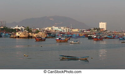fishing boats on river against building resort city at dawn