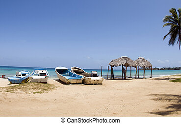 fishing boats on Waula Point Paraiso beach with thatch roof huts Big Corn Island Nicaragua Central America view of Brig Bay