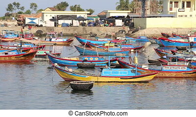 fishing boats roll in bay against small village at dawn