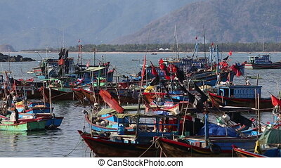 fishing boats roll in sea bay against mountains at dawn