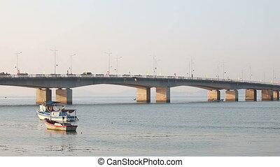 fishing boats roll on river near bridge at dawn