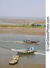 fishing boats sailing in the water in northern china