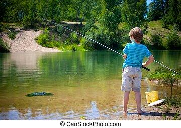 A little boy fishing in a lake.