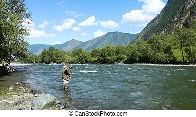 Fishing by flyfishing on the river. Russia Siberia. River Chelushman