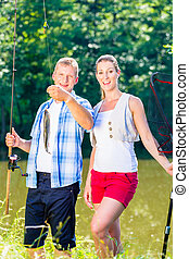 Fishing couple, man and woman, on lake being proud of catch
