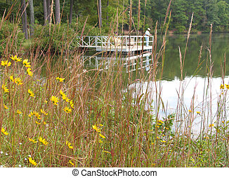 fishing dock - Man Fishing off a dock at a lake with yellow...