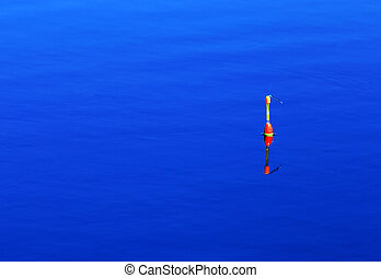 Fishing float on the blue surface o