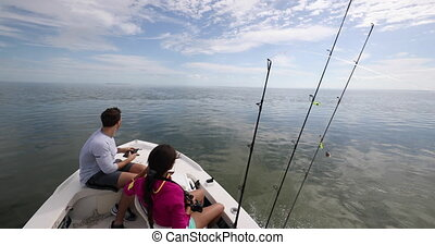 Fishing from boat - people going fishing with fishing rod on open water. Man and woman going shark fishing in the Keys, Florida, USA.