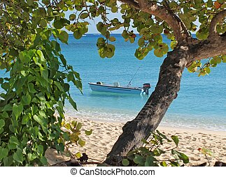 A lone fishing boat in the Caribbean beside a deserted Cayman Islands Beach
